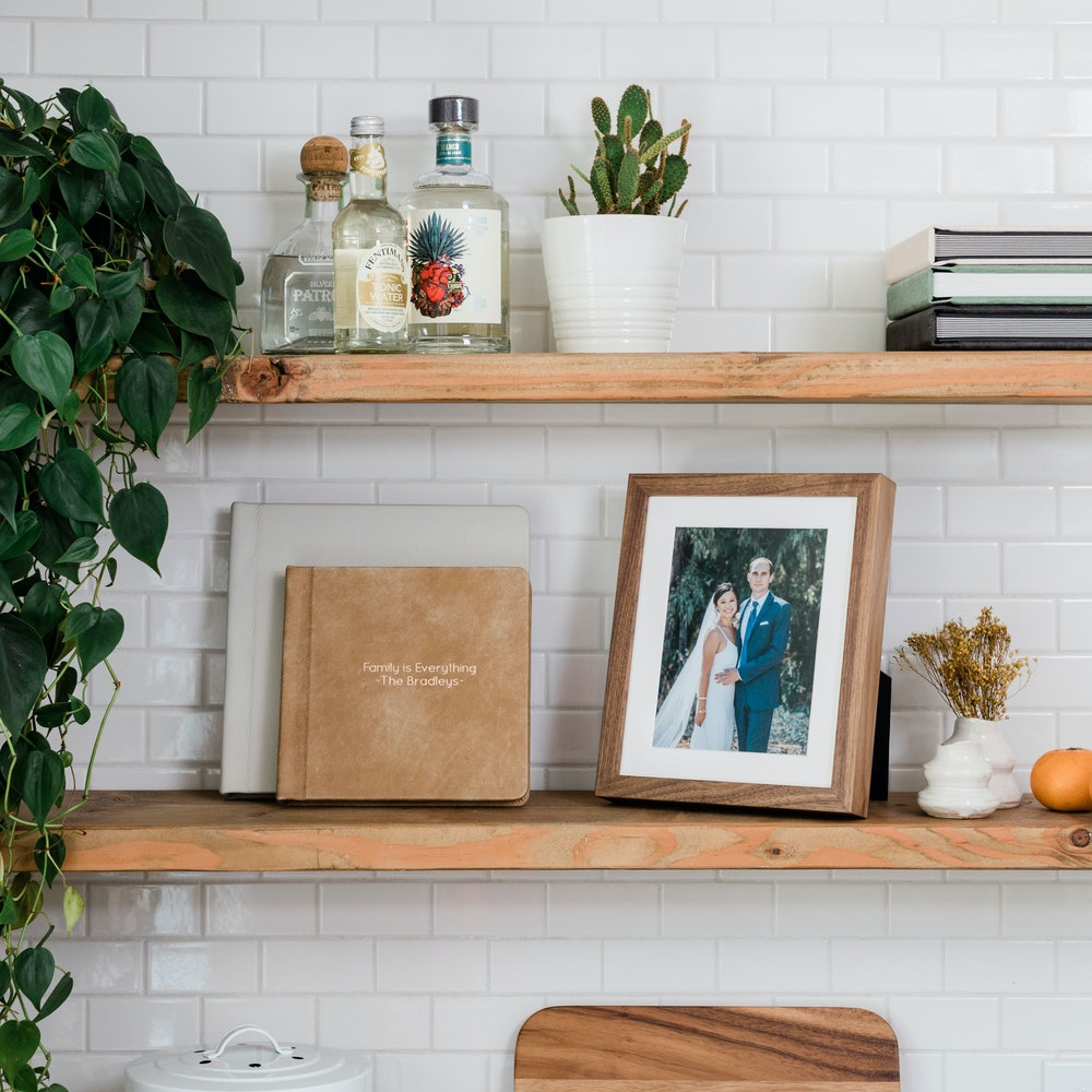 Walnut Woodland Framed Tabletop Print on kitchen shelf with leather Albums
