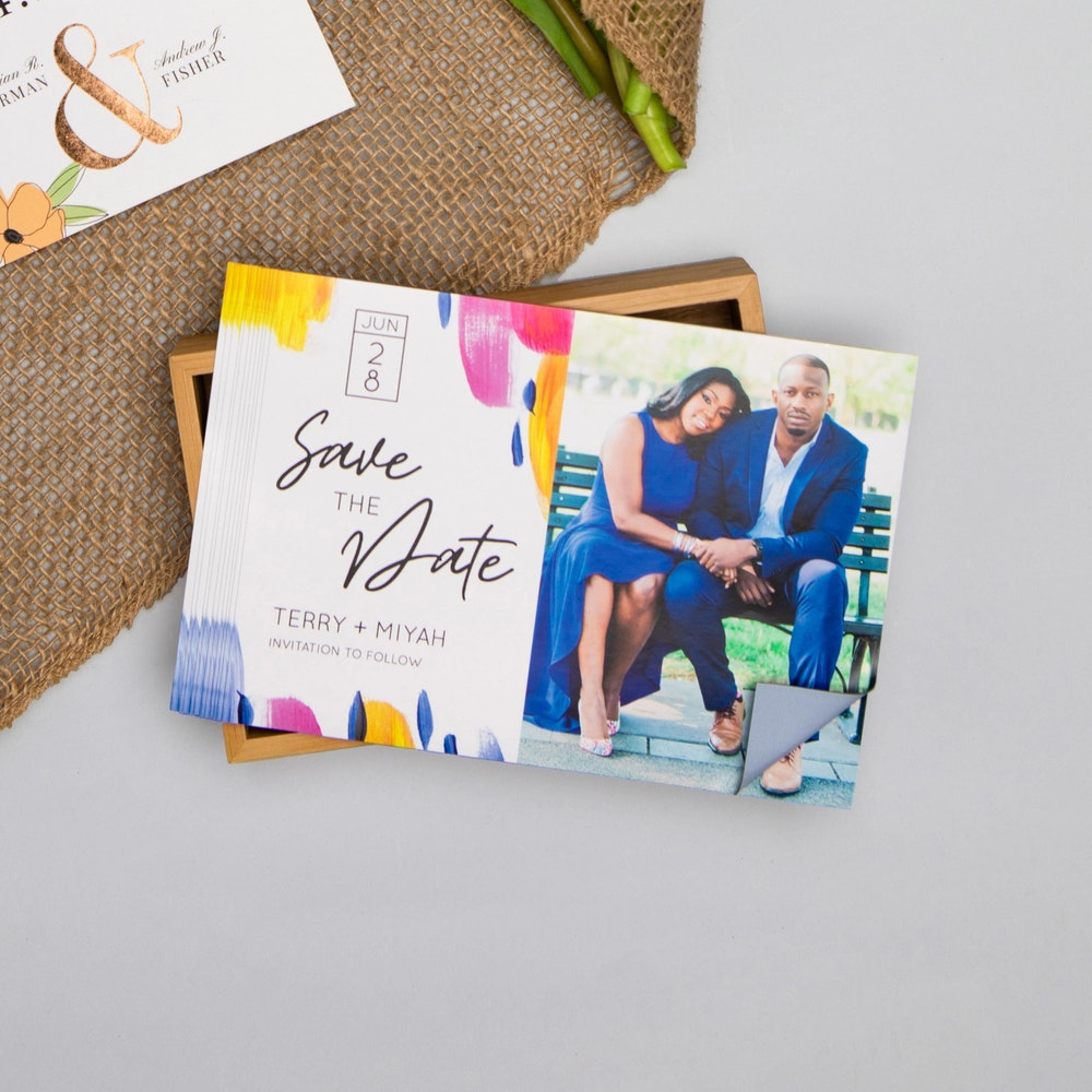 Stack of Magnet save the date cards on wood box