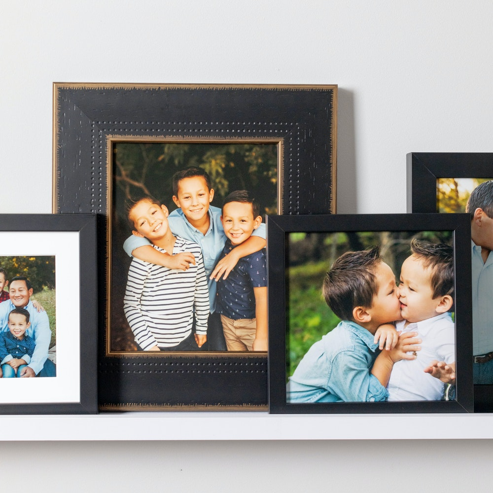 Multiple Framed Tabletop Prints layered on picture rail shelf