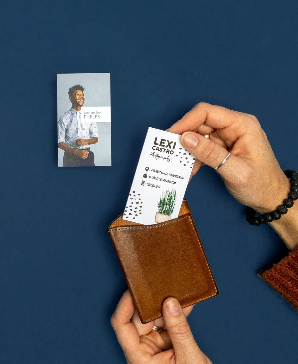 Hand placing Business Cards into wallet