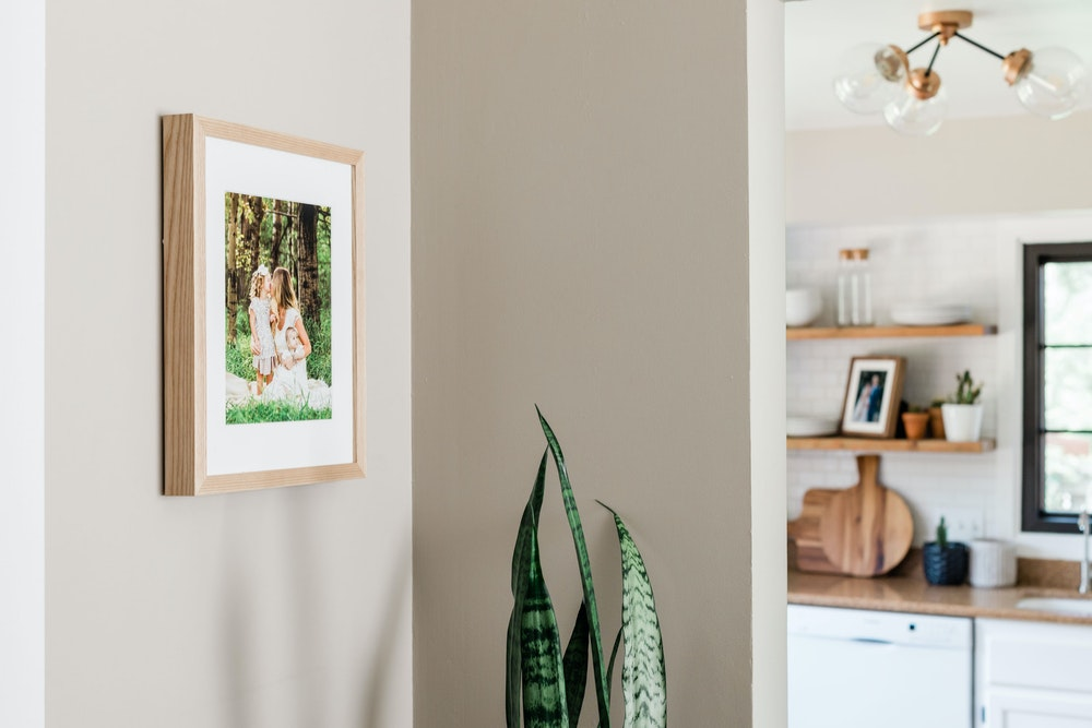 Natural Woodland Framed Print with white mat hanging in kitchen hallway